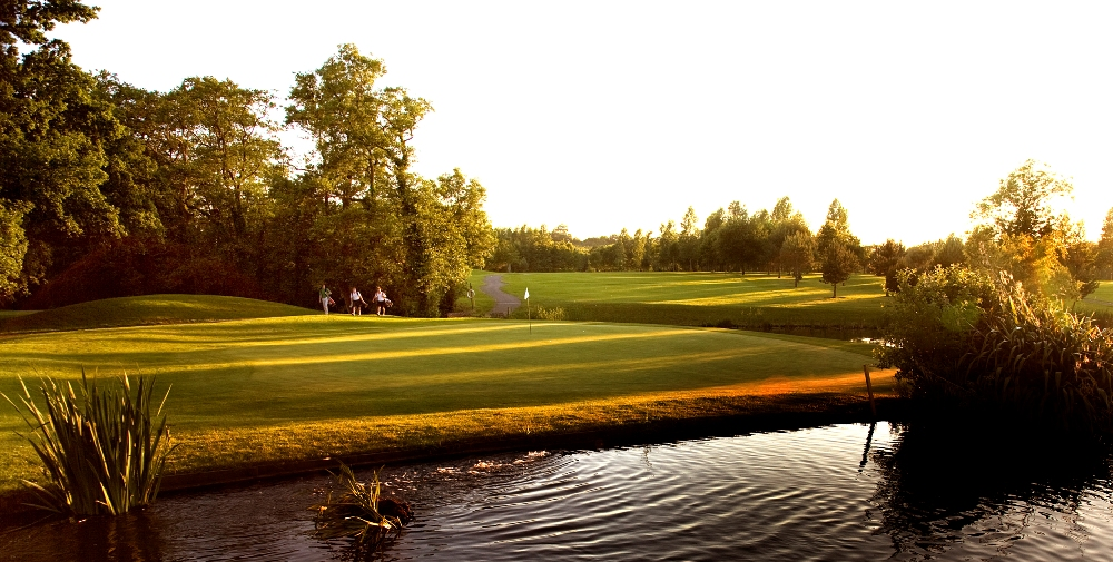 Golfers playing on the Lake Course at the Vale resort