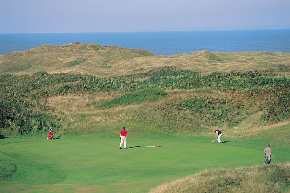 Golfers playing on Pyle and Kenfig golf course