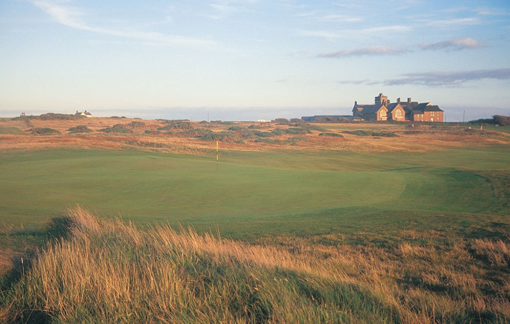 Hole and clubhouse on the Royal Porthcawl golf course