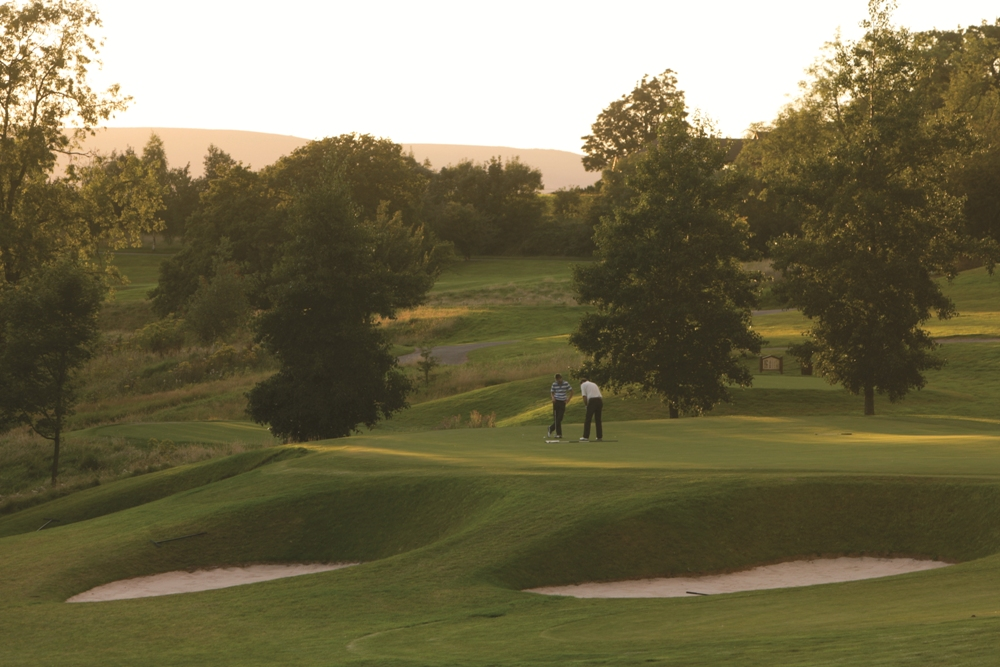 Golfers putting on the Montgomerie course at Celtic Manor