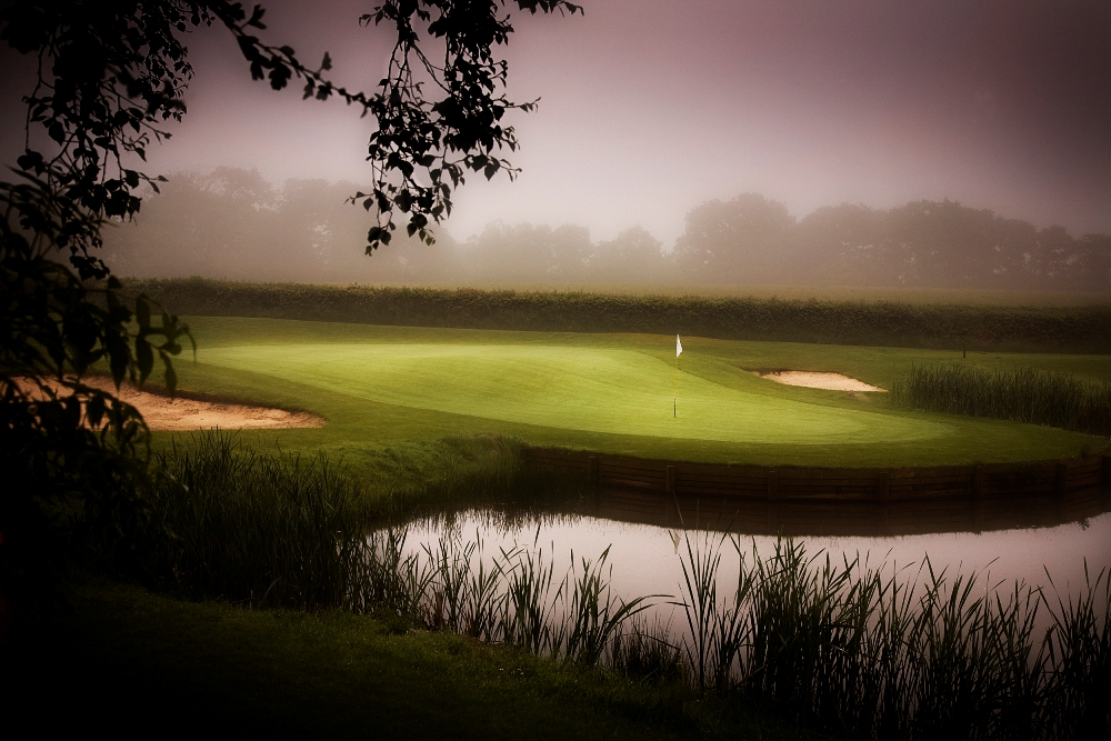 Undulated green and lake on the Wales National course at the Vale resort