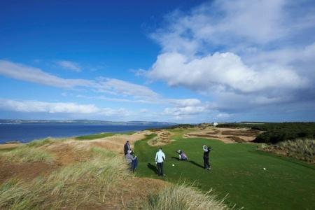 Golfers playing the Par 3 8th at Castle Stuart