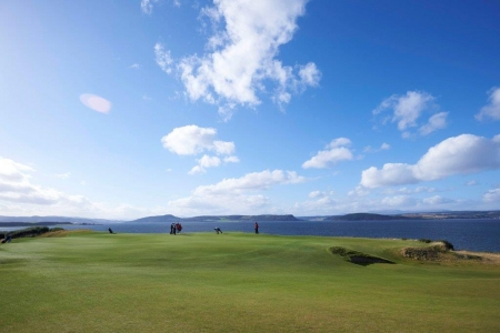 Golfers putting on the 18th green at Castle Stuart