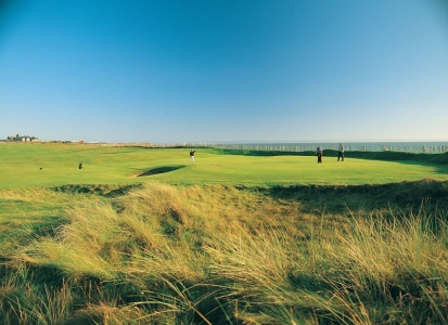 Golfers putting on the Royal Porthcawl golf course
