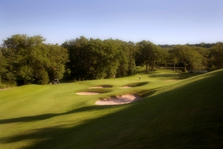 Golfers putting on the Lake Course at the Vale resort