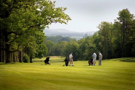 Golfers playing on the Wales National course at the Vale resort