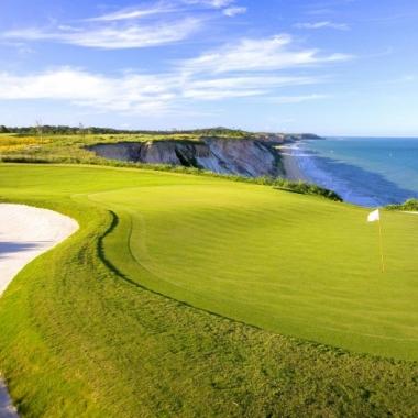 Bild einer Golfanlage zwischen Bunker und Strand