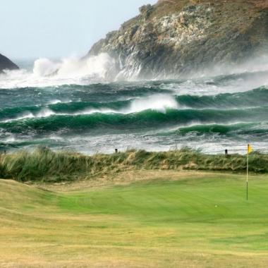 Bild vom Blick eines Loches der Golfanlage auf an zerklüfteten Klippen brechende hohe Wellen