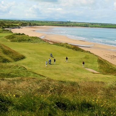 Golfers playing on a hole next to sandy beach and ocean