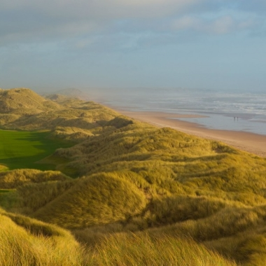 Image of golf green, grassy dunes and sandy beach with ocean