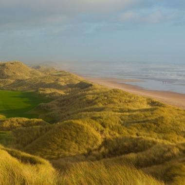 Bild einer Golfanalge, grasige Dünen und Sandstrand mit Meer