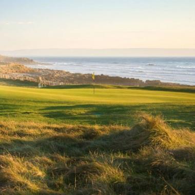 Bild einer Golfanlage mit Steinstrand und Meeresblick
